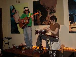 Two guys playing music on a tiny stage in front of somewhat homoerotic paintings of superheros